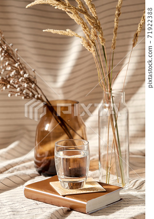 glass of water, decorative dried flowers in vases 71922388