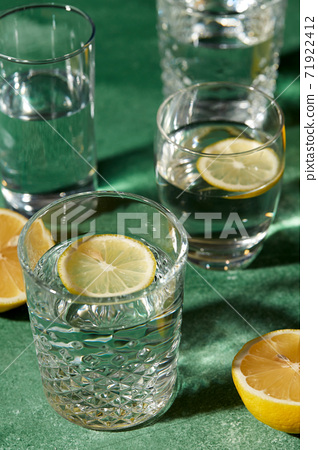 glasses with water and lemons on green background 71922412