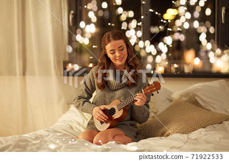 happy young woman playing guitar in bed at home 71922533