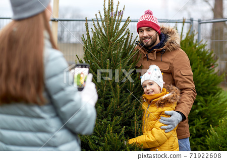 family taking picture of christmas tree at market 71922608
