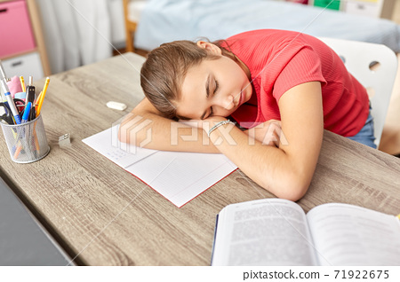 tired student girl sleeping on table at home 71922675