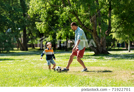 father with little son playing soccer at park 71922701
