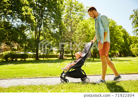 happy father with child in stroller at summer park 71922804