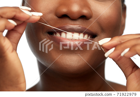 african woman cleaning teeth with dental floss 71922979