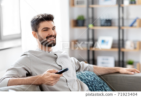 happy man with remote control watching tv at home 71923404