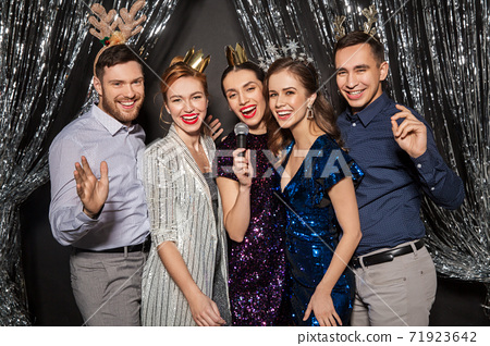 friends with microphone singing at christmas party 71923642