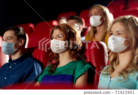 people in masks watching movie in theater 71923901