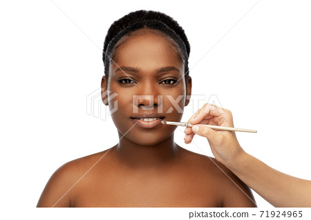 face of african woman and hand with make up brush 71924965