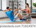 man with personal trainer doing sit ups at home 71924974