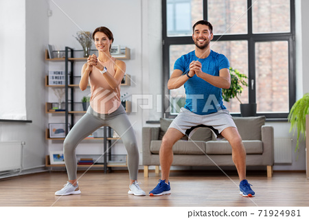 happy couple exercising and doing squats at home 71924981