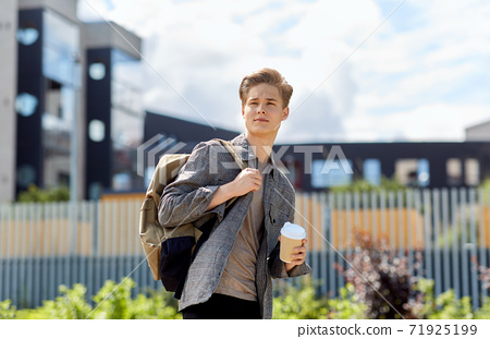 young man with backpack drinking coffee in city 71925199