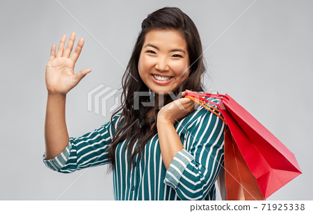 happy asian woman with shopping bags waving hand 71925338