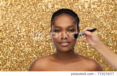 african woman and hand with make up brush 71925657