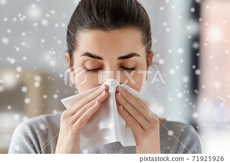 sick woman blowing nose in paper tissue at home 71925926