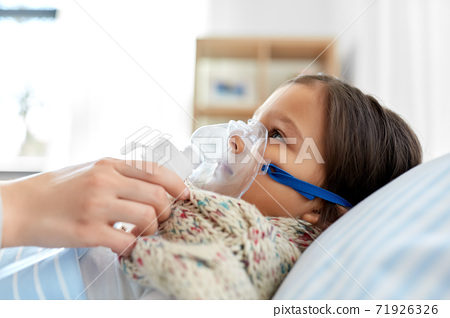 mother and sick daughter with oxygen mask in bed 71926326