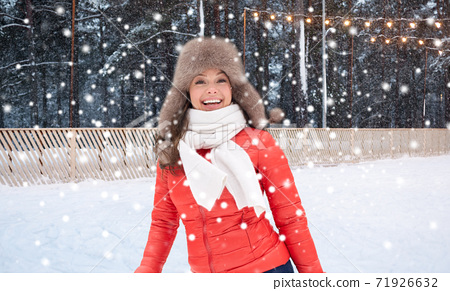 happy woman in winter hat over ice skating rink 71926632