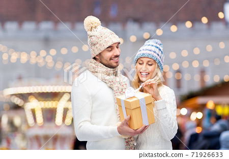 smiling couple in winter clothes with gift box 71926633