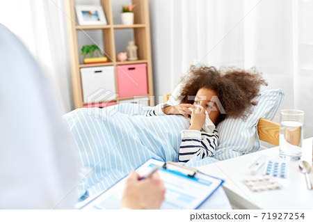 doctor with clipboard and sick girl in bed at home 71927254