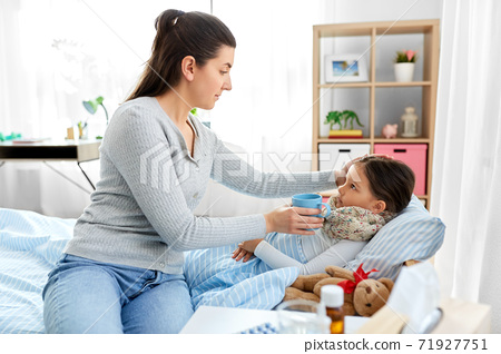 mother giving tea to sick daughter lying in bed 71927751