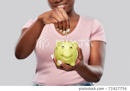 close up of woman with coin and piggy bank 71927756
