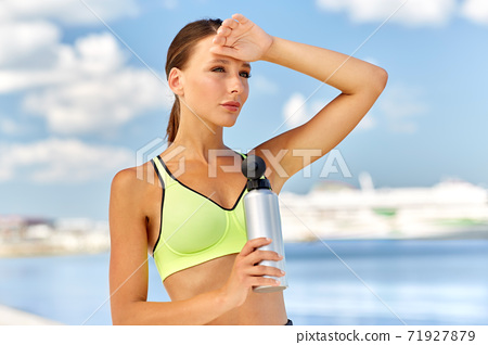 woman drinking water from bottle after sports 71927879