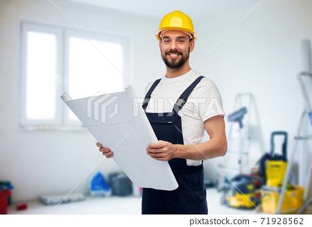 male worker or builder in helmet with blueprint 71928562