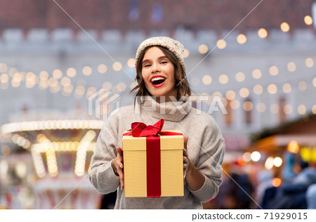 happy young woman in hat holding chrismas gift 71929015