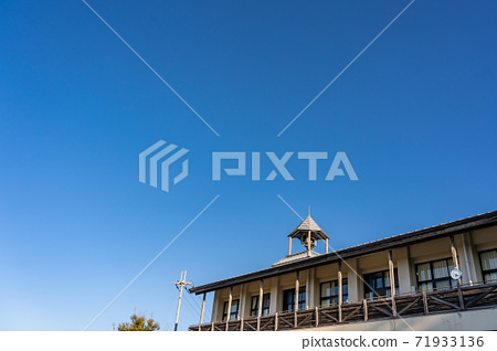 Bell on the roof of an old school, pointed roof 71933136