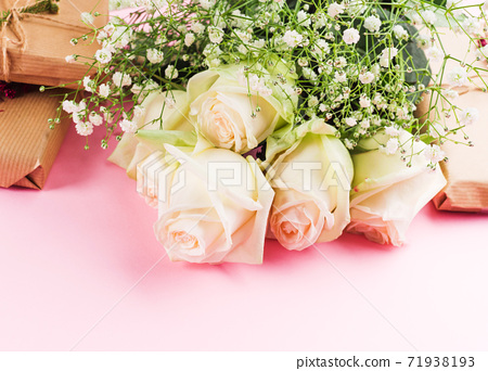 White roses and gifts on pastel pink background 71938193