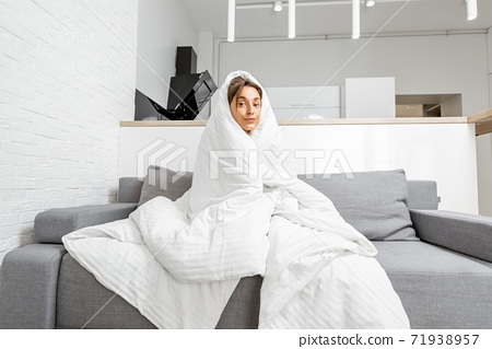 Woman covered with a blanket on the couch at home 71938957