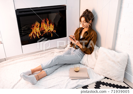 Woman relaxing near the fireplace at home 71939005