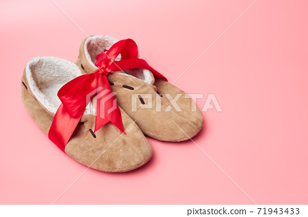winter slippers with fur in a red ribbon, on a blue background, banner, copy space, mock up 71943433