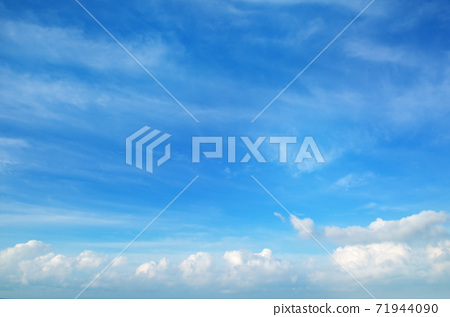 A clear blue sky with white clouds 71944090