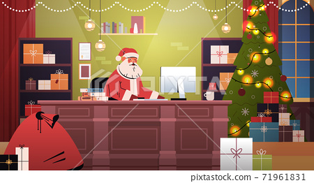 santa claus sitting at workplace and using computer merry christmas happy new year holidays celebration 71961831