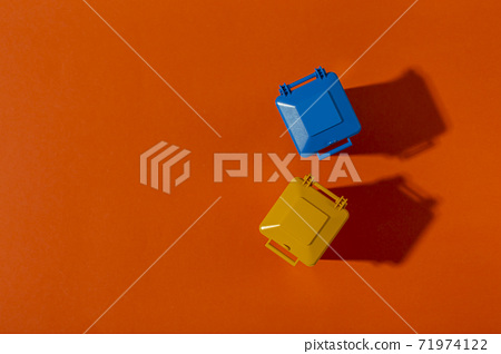 The trash containers in blue and yellow colors on orange background. 71974122