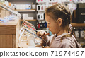 Little child girl using new smartphone on counter in an electronics store. 71974497