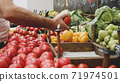 Close-up hands of grocery worker is arranging vegetables on store shelves 71974501