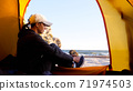 Woman is puts her shoes while sits in camping tent at beautiful beach 71974503