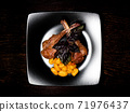 Grilled meat on a plate. Restaurant food. Lamb rack dish with pasta. 71976437