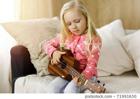 Little cute baby playing ukulele guitarin sunny room. Childhood concept 71991630