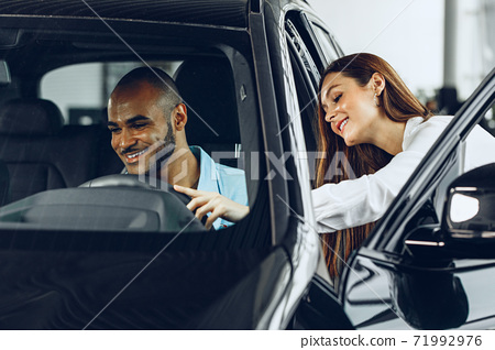Young woman salesperson in car showroom showing a car to her male client 71992976