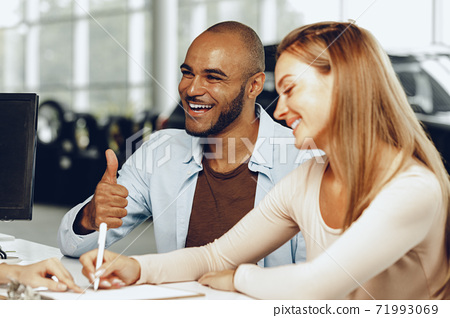 Happy couple signing contract at car dealership 71993069