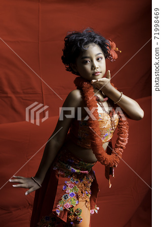 A young Asian schoolgirl dresses in southern Thai tribal clothing and accessories to perform a stage dance. 71998469