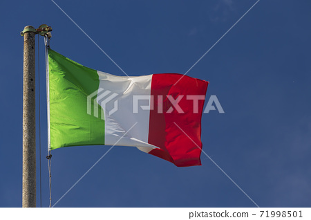 Italian flag blowing in the wind in the blue sky 71998501