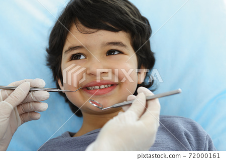 Cute arab boy sitting at dental chair with open mouth during oral checking up with doctor. Visiting dentist office. Stomatology concept 72000161