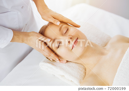 Beautiful caucasian woman enjoying facial massage with closed eyes in sunny spa salon. Relaxing treatment in medicine and Beauty concept 72000199