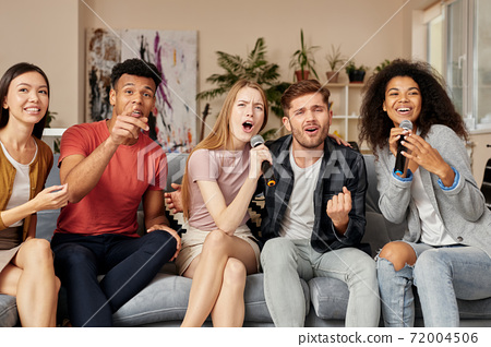 Add music to your party. Group of excited young multicultural friends playing karaoke at home, singing with microphone while sitting on the couch in the living room 72004506