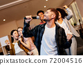 Feel like a superstar. Cheerful handsome young guy singing holding microphone while playing karaoke with friends at home, standing in the modern apartment 72004516