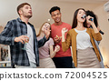 Let your soul speak. Young beautiful asian woman holding microphone and singing while having fun with friends at home. Playing karaoke at home.  72004525