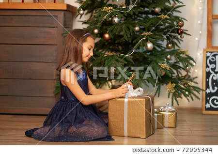 Happy childhood, Christmas magic fairy tale. Little girl dreams before opening Santa's present for Christmas 72005344